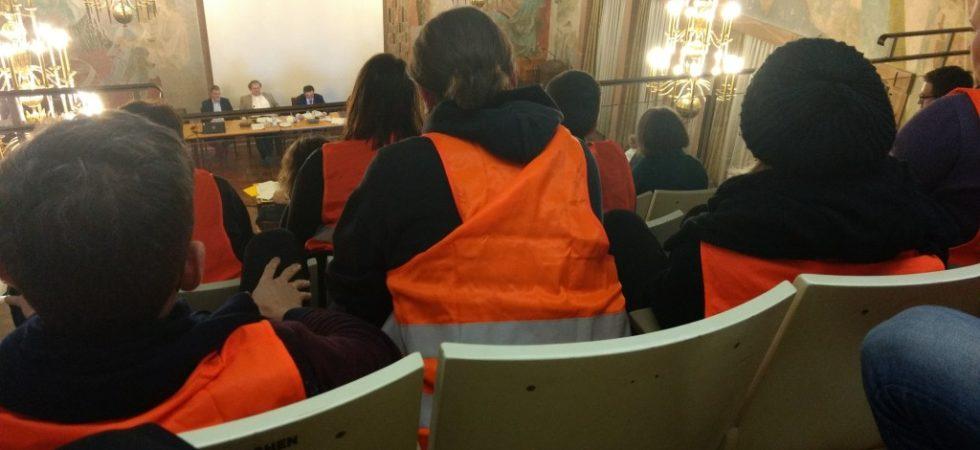 Bild aus Stadtratssitzung. Zuschauer in orangenen Westen
